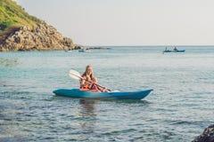 Mutter und Sohn, die in tropischem Ozean Kayak fahren stockbild
