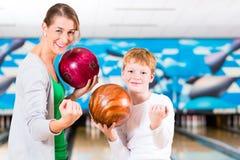 Mutter und Sohn, die zusammen in der Bowlingspielmitte spielen Lizenzfreie Stockfotos