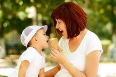 Mutter und Sohn, die zusammen Eiscreme im Waffelkegel am sonnigen Tag essen Glückliches Familienspaßkonzept lizenzfreie stockfotografie