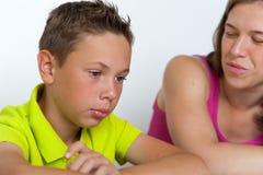 Mutter und Sohn, die zusammen Hausarbeitlektionen tun Lizenzfreie Stockbilder