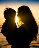 Mutter und Sohn in einem tiefen Moment der Liebe während des Sonnenuntergangs am Strand Lizenzfreie Stockfotografie