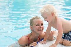 Mutter und Sohn haben Spaß durch einen Swimmingpool Lizenzfreie Stockfotografie