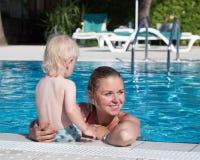 Mutter und Sohn haben Spaß durch einen Swimmingpool Lizenzfreies Stockbild