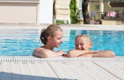 Mutter und Sohn haben Spaß durch einen Swimmingpool Stockfotos
