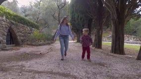 Mutter und Sohn im zufällige Kleidungs-Weg im Park stock video