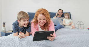 Mutter-und Sohn-Lachen unter Verwendung der Tablet-Computer-Uhr-lustigen Videos, die zusammen auf Bett in der Schlafzimmer-Famili stock video