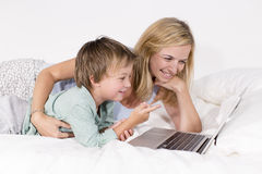 Mutter und Sohn liegen mit Notizbuch auf einem Bett Lizenzfreie Stockfotografie