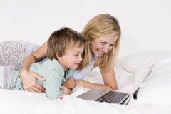 Mutter und Sohn liegen mit Notizbuch auf einem Bett Stockfotos