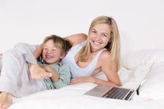Mutter und Sohn liegen mit Notizbuch auf einem Bett Stockfoto