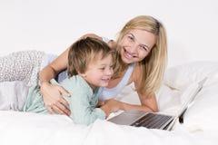 Mutter und Sohn liegen mit Notizbuch auf einem Bett Lizenzfreies Stockfoto