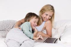 Mutter und Sohn liegen mit Notizbuch auf einem Bett Lizenzfreie Stockfotos