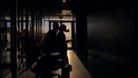 Mutter und Sohn mit Auflage im Flughafenabfertigungsgebäude bei Sonnenuntergang stock video