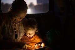 Mutter und Sohn mit Auflage während der Autoreise nachts stockfoto