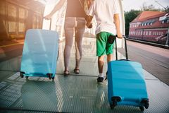 Mutter und Sohn mit blauem Gepäckkoffer gehend auf Bahnstationsplattform stockbilder