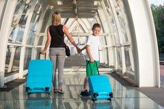 Mutter und Sohn mit blauem Gepäckkoffer gehend auf Bahnstationsplattform lizenzfreies stockfoto