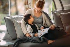 Mutter und Sohn mit Geschichtenbuch zu Hause stockfotografie
