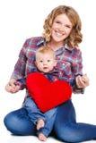 Mutter und Sohn mit rotem Herz-förmigem Kissen Lizenzfreies Stockbild