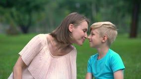 Mutter und Sohn nuzzling, Zeit zusammen verbringend draußen, Einheit der liebevollen Familie stock video