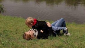 Mutter und Sohn sind Lügen auf dem Gras auf Flussbank stock video footage