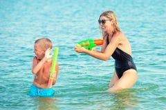Mutter und Sohn spielen auf dem Strand mit Wasserpistolen Junge Erwachsene lizenzfreie stockbilder