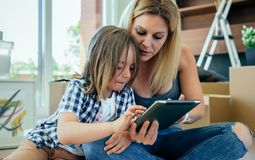 Mutter und Sohn, welche die Tablette spielen lizenzfreie stockfotos