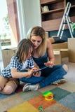 Mutter und Sohn, welche die Tablette spielen stockbilder