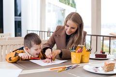 Mutter und Sohn zeichnen farbige Bleistifte der Zeichnung Hände Stockfotos