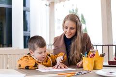 Mutter und Sohn zeichnen farbige Bleistifte der Zeichnung Hände Lizenzfreies Stockfoto