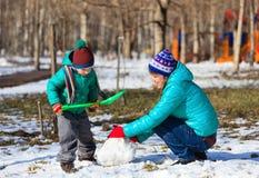 Mutter- und Sohngebäudeschneemann im Winter Stockfotos