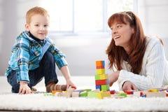 Mutter- und Sohngebäude ragen zusammen lächelnd hoch Lizenzfreie Stockfotos