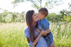 Mutter- und Sohnporträt gegen grüne Baumfamilie stockbild