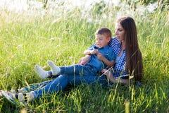 Mutter- und Sohnporträt gegen grüne Baumfamilie lizenzfreie stockfotos