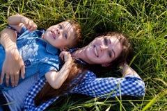 Mutter- und Sohnporträt gegen grüne Baumfamilie stockfotos