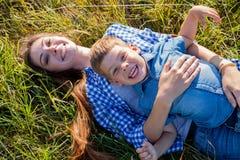 Mutter- und Sohnporträt gegen grüne Baumfamilie stockfotografie