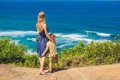 Mutter- und Sohnreisende auf einer Klippe über dem Strand Leeres Paradies stockfoto