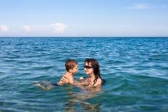 Mutter- und Sohnschwimmen im Meer lizenzfreie stockbilder
