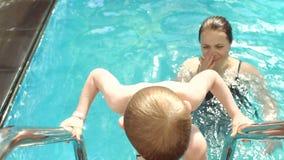 Mutter- und Sohnschwimmen im Pool, das Kind verlässt ein Wasser auf der Treppe