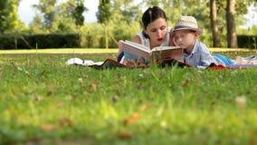 Mutter und Sonne liegen im Park während des Picknicks, das ein Buch von Geschichten liest stock video