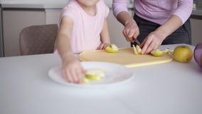 Mutter und Töchter, die zu Hause gesundes Lebensmittel kochen und Spaß haben Gelber Apfel des Ausschnitts der jungen Frau auf dem stock video footage