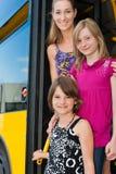 Mutter und Töchter, die aus einem Bus heraus schauen Stockbilder