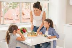 Mutter und Töchter, die gesundes Lebensmittel essen stockbild