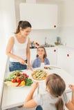 Mutter und Töchter, die gesundes Lebensmittel essen lizenzfreies stockbild