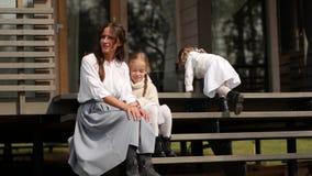 Mutter und Töchter sitzen auf Schritten vor Haus stock footage