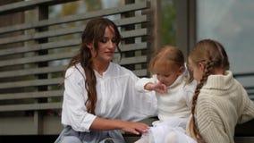 Mutter und Töchter sitzen auf Schritten vor Haus stock video