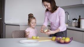 Mutter und T?chter, die zu Hause gesundes Lebensmittel kochen und Spa? haben Gelber Apfel des Ausschnitts der jungen Frau auf dem stock footage