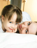 Mutter und Tochter auf dem Bett Stockbilder