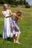 Mutter und Tochter auf dem Gebiet, das Spaß und das Tanzen hat Lizenzfreie Stockbilder
