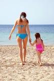 Mutter und Tochter auf dem sandigen Strand. stockfotos