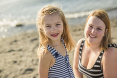 Mutter und Tochter auf dem Strand versehen mit Seiten, Spaß habend lizenzfreies stockbild