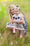 Mutter und Tochter auf der Art des Spielens mit Luftblasen Stockbild